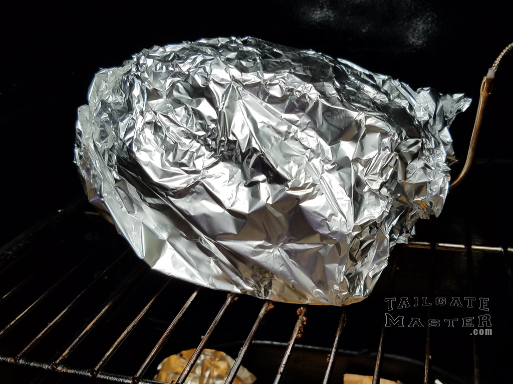 boston butt wrapped in aluminum foil and back in the smoker