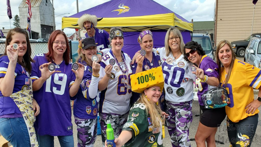 group of Minnesota Vikings and green bay packers fans in front of a tailgating canopy
