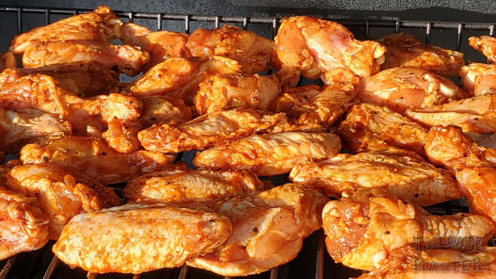 chicken wings on the top rack of a charcoal smoker